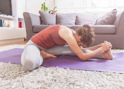 Woman doing Yoga exercise at Home, Janu Sirsasana pose ,workout in living room on fitness mat, healthy lifestyle
